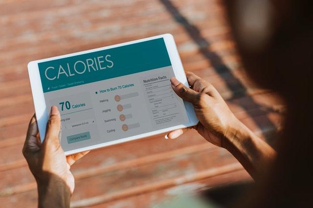 drží tablet s otevřenou aplikací na kalorie