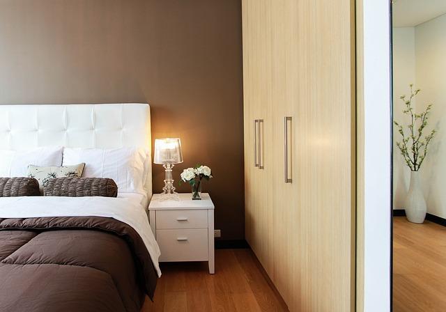 postel a vedle moderní vestavěná šatní skříň