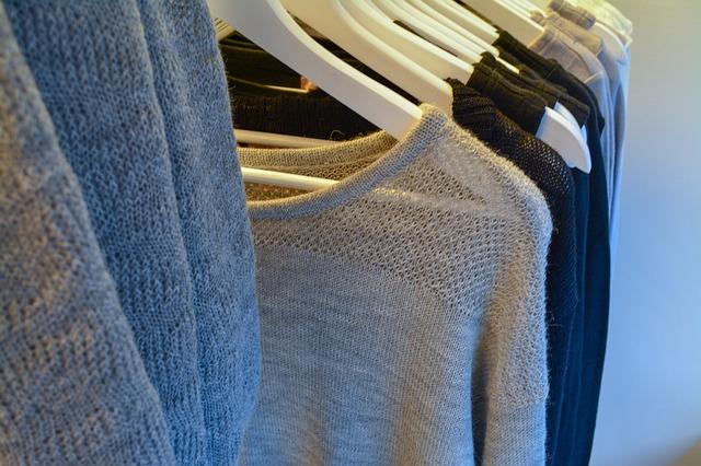 uspořádané svetry na věšácích