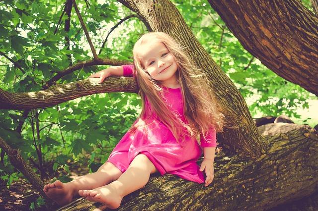 Malá slečna na stromě v růžových šatičkách, s dlouhými vlásky a s širokým úsměvem.jpg