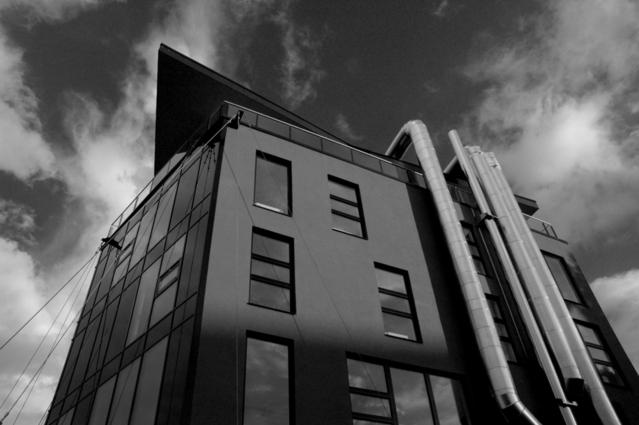 Černobílá fotografie budovy pohled nahoru, na jedné straně velké roury
