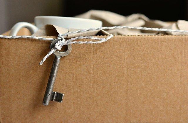 Stěhování-papírová krabice s nádobím, kolem krabice připevněný provázek s klíčem od bytu