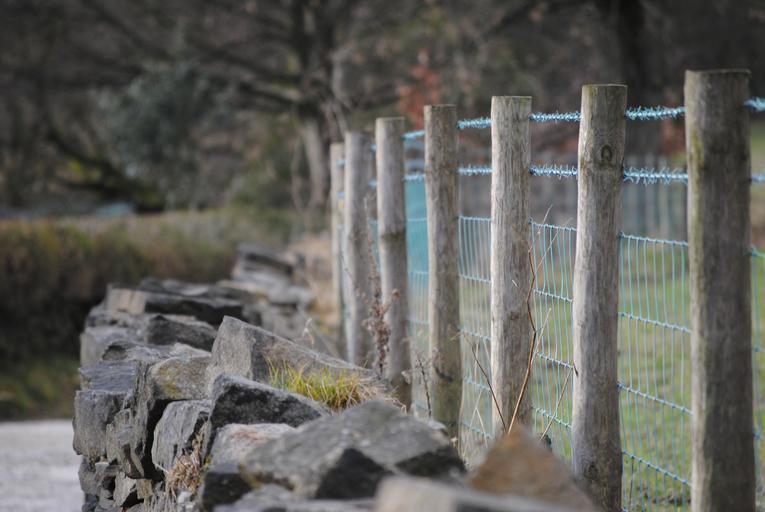 dřevěný plot podložený kameny