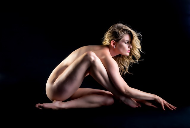 a naked model in a pose on the dark background